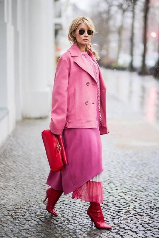 un look super audacieux avec une robe rose, une jupe rose et blanche, des bottes rouges, un manteau court rose vif et un sac rouge