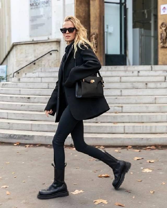 un look totalement noir avec un pull, des skinnies, des bottes de combat, un manteau court et un sac