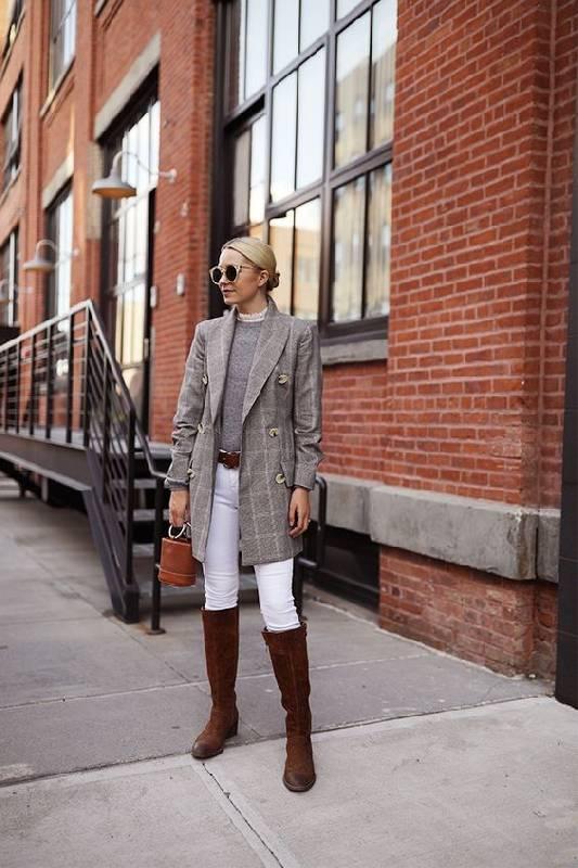 une tenue preppy avec un haut gris, un blazer gris à carreaux, des skinnies blancs, des bottes marron et un sac à seaux marron