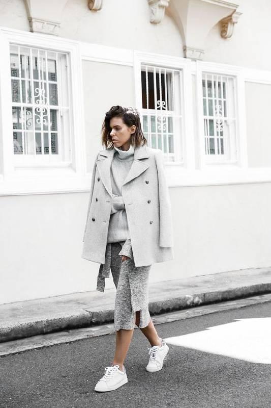 un look monochrome avec un pull oversize, une jupe midi en tricot, des baskets blanches, un manteau court
